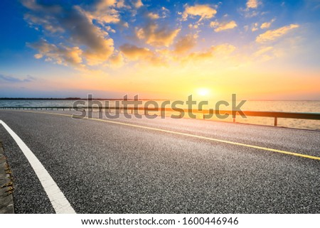 Empty asphalt road and lake with dreamy clouds at sunset. #1600446946
