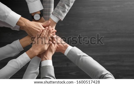 People holding hands together over grey wooden background, top view. Unity concept #1600517428