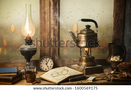 Classic still life with hot tea pot placed with illuminated vintage lamp, old books, cup of tea on rustic wooden table.  Royalty-Free Stock Photo #1600569175