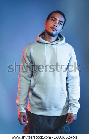 Vertical picture of calm peaceful attractive egyptian or hispanic young man posing on camera alone and look down. Wear jeans pants and blue hoodie. Coll handsome guy isolated on background
