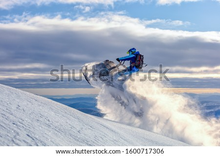 a snowmobile rider jumps in a mountain valley at dawn. sports snow bike with snow splashes and snow trail. bright snowmobile and suit without brands. snowmobilers sports riding. stock photo #1600717306