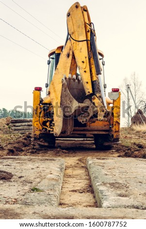 The excavator installs concrete slabs for the road. #1600787752