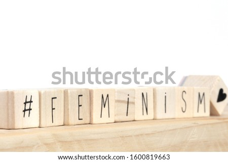 Wooden cubes with a hashtag and the word Feminism near white background, social media concept close-up #1600819663