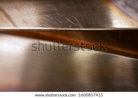 Curved copper sheet of various shapes. Glare on sheets of copper. Curved copper sheets close-up. Reflection on sheets of copper. #1600857415