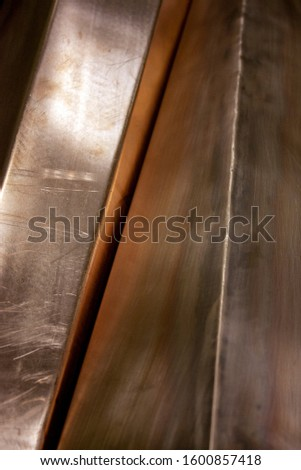 Curved copper sheet of various shapes. Glare on sheets of copper. Curved copper sheets close-up. Reflection on sheets of copper. #1600857418