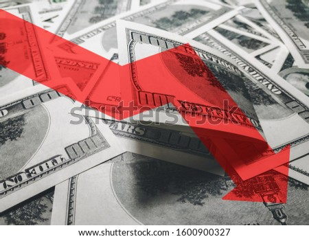The light red arrow icon on a background of money. The concept of changing course of US dollar on the market. Devaluation, collapse, stagnation of the economy. #1600900327