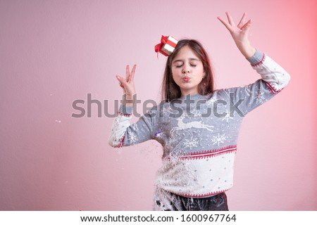 Playfull brunette girl with closed eyes and raised hands, dressed in santa sweater and hat, stained in synthetic snow, isolated over pink background, studio photo