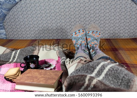 Rest reading a book. Female legs in warm socks. A warm wool blanket with a tray of coffee and cookies on it. Nearby lies a book. #1600993396