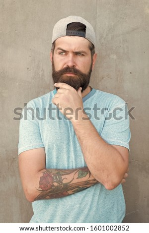 To beard or not to beard. Thoughtful hipster thinking on grey wall. Hipster touching thick beard hair on unshaven face. Bearded man in trendy hipster style. Brutal hipster wearing casual baseball cap. #1601002852