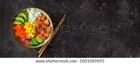 Top view of poke bowl with salmon and avocado on dark background Royalty-Free Stock Photo #1601069695