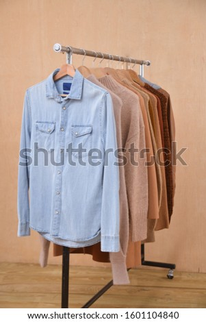 long sleeve light blue jeans shirt and brow knitwear ,sweater and brown jacket are hanging on Clothes Hanger,-wooden background  #1601104840