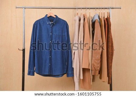 long sleeve blue jeans shirt and brow knitwear ,sweater and brown jacket are hanging on Clothes Hanger,-wooden background  #1601105755