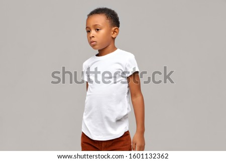 Half-profile picture of casually dressed African boy in white t-shirt having calm confident facial expression posing isolated against blank studio wall background with copy space for your information