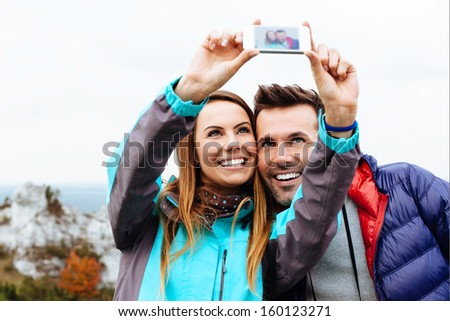 Happy couple taking snapshot of themselves