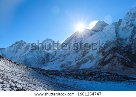 Sun rises right above West Ridge of Everest mountain in Himalayas. View from the slope of Kala Patthar mountain. Theme of travel in Nepal. #1601254747