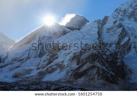 Sun rises right above West Ridge of Everest mountain in Himalayas. View from the slope of Kala Patthar mountain. Theme of travel in Nepal. #1601254750