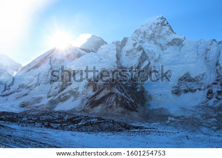 Sun rises right above West Ridge of Everest mountain in Himalayas. View from the slope of Kala Patthar mountain. Theme of travel in Nepal. #1601254753
