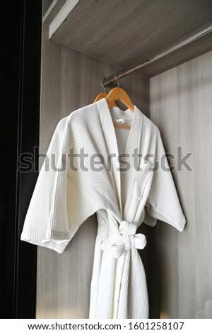 Closeup shot of a white terry cloth bathrobe on a hangers. White bathrobe hanging in a closet. #1601258107