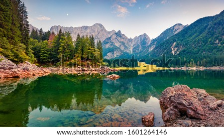 Picturesque morning view of Julian Alps. Splendid sunrise on Fusine lake. Majestic outdoor scene with Mangart peak on background, Province of Udine, Italy. Beauty of nature concept background. #1601264146