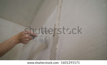 Worker aligns the wall with a spatula. Worker aligns the wall with construction putty. a close shot at the builder hands, who level the wall with a long spatula and plaster, the man applies the #1601295571