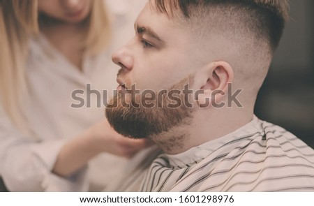 beautiful bearded man cutting the hair and beards in the barbershop #1601298976