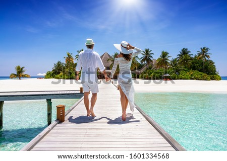 A happy traveler couple in white summer clothing walks down hand in hand a wooden pier towards a tropical paradise island in the Maldives, Indian Ocean #1601334568