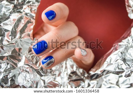 Young woman's hand with beautiful manicure blue on red background with metallic shiny paper. 2020 color trend. #1601336458