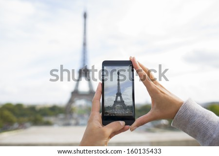 Woman in Paris taking pictures with a Cell phone in front of Eiffel Tower