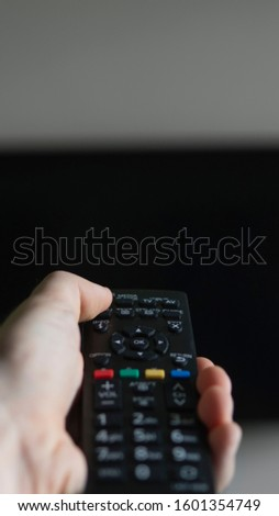 The man with the remote control in hand want switch on the TV and presses the button on the remote control. Remote control in hand closeup. #1601354749