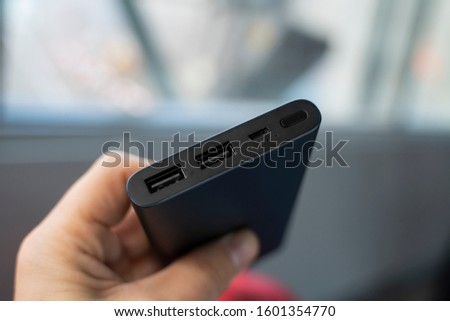 Man is holding the power bank a an the charger. Powerbank in hand. Power-saving device for smartphone and other devices. Helping to charge your phone. #1601354770