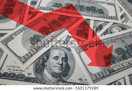 The light red arrow icon on a background of money. The concept of changing course of US dollar on the market. Devaluation, collapse, stagnation of the economy. #1601379289