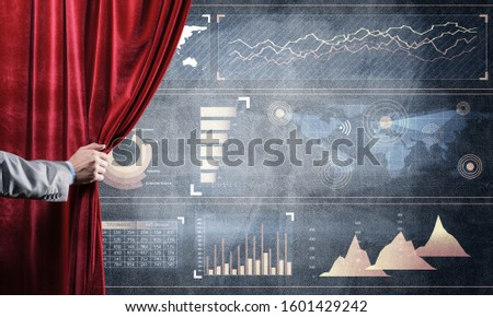 Hand opening red curtain and drawing business graphs and diagrams behind it #1601429242