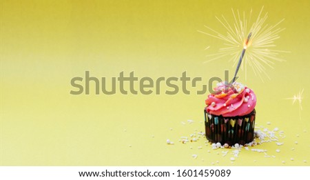 Festive cupcake with cream and decoration with sparkler on a yellow background. Concept photo for holiday, party, congratulations. Blank for banner #1601459089