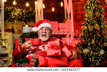 Delivering gifts. Winter vacation. Elderly grandpa at home. Traditions concept. Santa Claus near christmas tree. Merry christmas. Bearded senior man Santa Claus. Santa Claus relaxing in arm chair. #1601469277