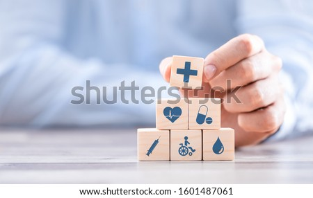 Hand arranging wood block with healthcare medical icon. Health insurance - concept. #1601487061