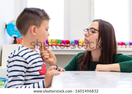Children speech therapy concept. Preschooler practicing correct pronunciation with a female speech therapist.  #1601496832