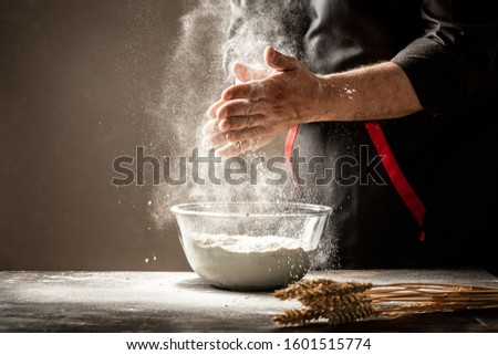 chef in black uniform sprinkles white wheat flour in different directions, product scatters dust, black background.Food concept. Male hands. #1601515774