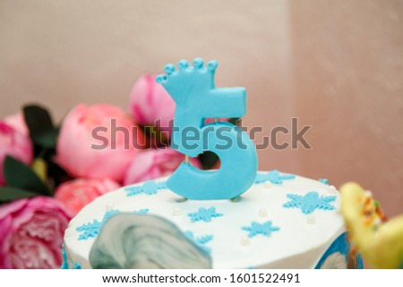 Blue candle with number 5 and crown on top of winter birthday cake with snowflakes. Frozen cartoon character thematic party.