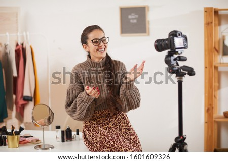 Portrait of contemporary young woman talking animatedly to camera while filming video vlog for beauty and lifestyle channel, copy space