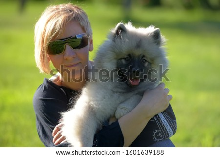 young blonde woman in summer sunglasses with keeshond wolfspitz puppy on a background of green grass #1601639188