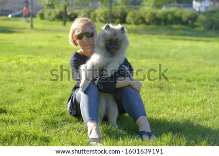 young blonde woman in summer sunglasses with keeshond wolfspitz puppy on a background of green grass #1601639191