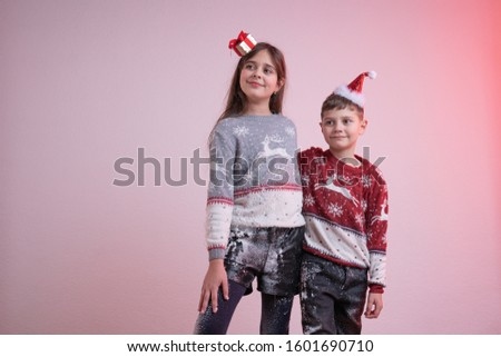 Children in santa sweaters and hats stained in synthetic snow isolated over pink background, brother hugs his sister, Merry Christmas and Happy New Year concept, studio photo