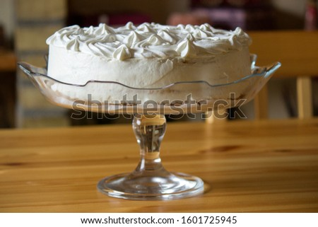 Front look Of A White Frosted Cake Placed On A Glass Plate.Wooden Table Below. #1601725945