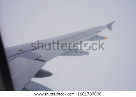 Wing surface equipped with aircraft flaps, spoilers (control surfaces) and winglet, at the right side of an airplane flying through thick clouds at high altitude, seen from the porthole of the plane #1601789098