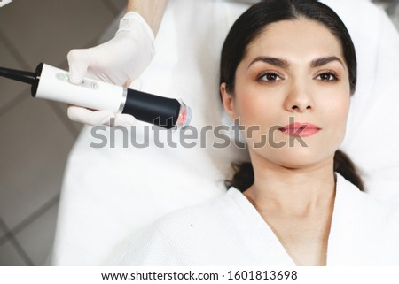 Young brunette lying on right side of picture and look up.Calm peaceful customer waiting for procedures. Beautician hold applicator or special machine for hydration. Procedure or spa treatment #1601813698