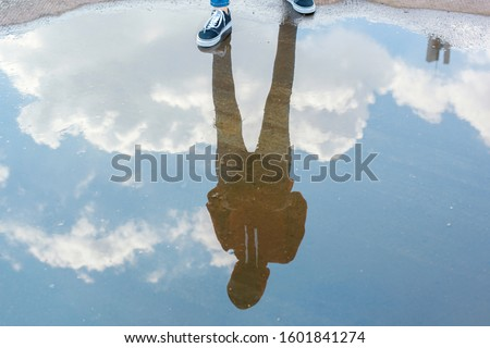 Reflection in water of man with casual style standing in bright blue sky  Royalty-Free Stock Photo #1601841274
