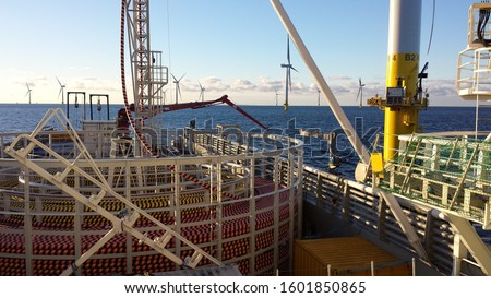 Cable-laying vessel lays cable at sea in a wind farm Royalty-Free Stock Photo #1601850865