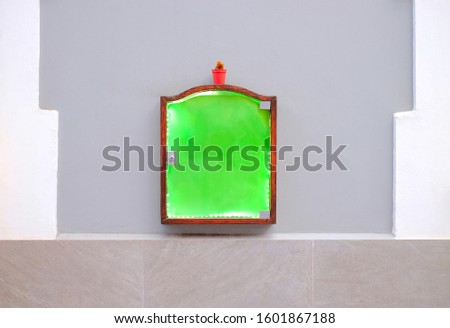 A green notice board and a flower pot on an empty wall. #1601867188