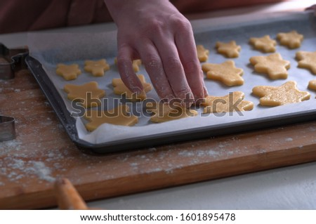 Cut cookies from rolled dough.Cook cuts cookies out of rolled dough. #1601895478