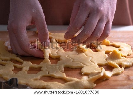 Cut cookies from rolled dough.Cook cuts cookies out of rolled dough. #1601897680